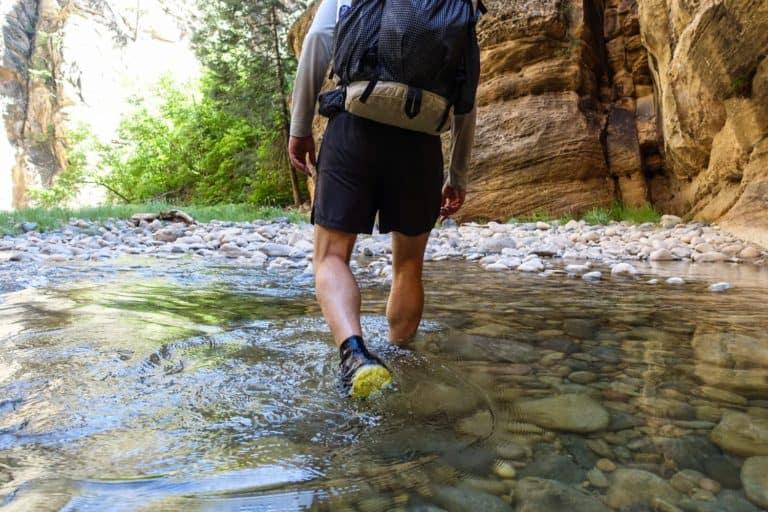 Mann läuft durch einen Bach mit leichten Wanderschuhen