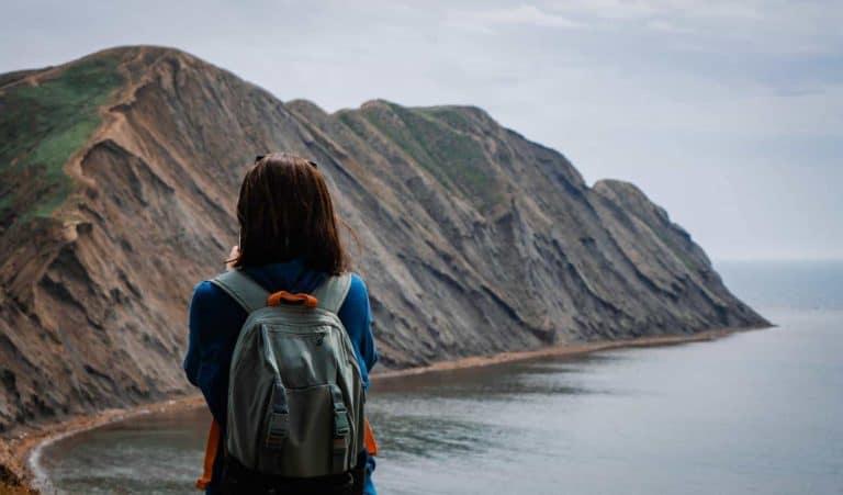 Frau mit Rucksack an Küste