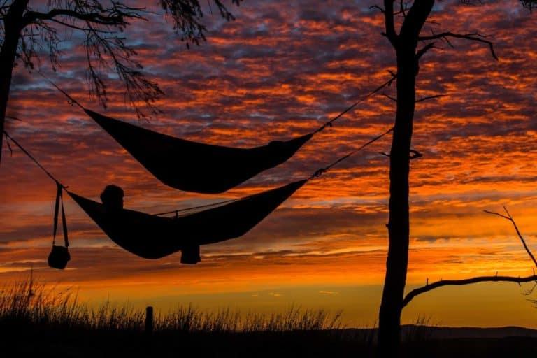Zwei Männer in Hängematten beim Sonnenuntergang